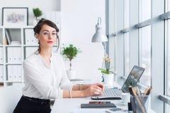 Jonge onderneemsterzitting op het haar werk, uitwerkend nieuwe bedrijfsideeën, dragend formele kostuum en glazen, het kijken Stock Foto