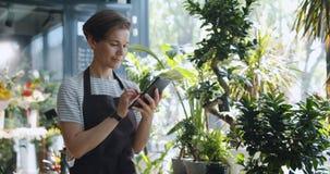 Jonge ondernemer die wat betreft het tabletscherm bloemen in de winkel van de bloemist bekijken stock footage