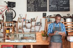 Jonge ondernemer die zich in zijn koffie bevinden die een digitale tablet gebruiken royalty-vrije stock afbeeldingen