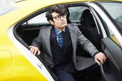 Jonge Ondernemer Leaving Taxi in Regen stock foto's
