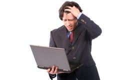 Jonge ongerust gemaakte bedrijfsmens die met laptop werkt Stock Foto