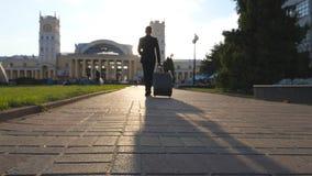 Jonge onherkenbare zakenman die op stedelijk milieu lopen en koffer op wielen trekken Succesvolle zeker stock footage