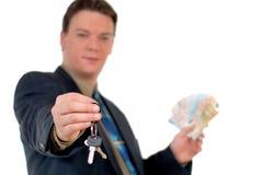 Jonge onroerende goederenagent het overhandigen sleutels, die geld tonen Stock Afbeeldingen