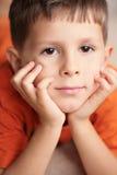 Jonge ontspannen jongen het glimlachen met handen op kin Royalty-vrije Stock Afbeelding