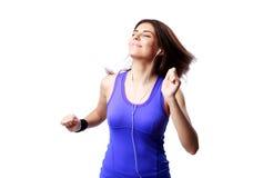 Jonge ontspannen sportvrouw die aan de muziek luisteren Stock Foto's