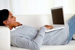 Jonge ontspannen vrouw die aan laptop werkt royalty-vrije stock afbeelding
