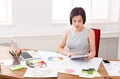 Jonge ontwerper die met blauwdrukken in het bureau werken stock afbeelding