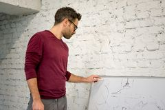 Jonge Ontwerper Drawing de Schets op Grote Whiteboard in Witte Studio royalty-vrije stock foto's