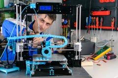 Jonge ontwerperingenieur die een 3D printer in laboratorium met behulp van stock foto's