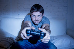 Jonge opgewekte mens die thuis op woonkamerbank het spelen videospelletjes zitten die afstandsbedieningbedieningshendel met behul Royalty-vrije Stock Afbeeldingen