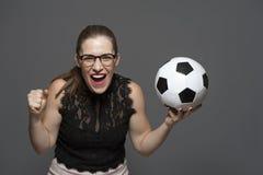 Jonge opgewekte van de de ventilatorholding van de vrouwenvoetbal het voetbalbal in handen stock foto