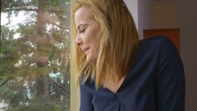 Jonge opgewekte vrouw die zich bij het venster en het golven bevinden stock video