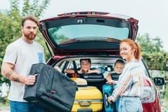 jonge ouders die bagage in boomstam van auto met jonge geitjes het kijken inpakken royalty-vrije stock afbeelding