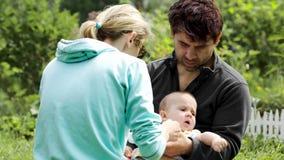 Jonge ouders die een babyjongen voeden openlucht stock video