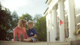 Jonge ouders die en hun aanbiddelijk kind houden koesteren Mooi licht stock video
