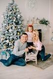 Jonge ouders die met baby dichtbij Kerstboom spelen royalty-vrije stock afbeelding