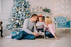 Jonge ouders die met baby dichtbij Kerstboom spelen royalty-vrije stock afbeeldingen