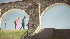 Jonge ouders die met hun aanbiddelijke zoon in binnenplaats lopen stock footage