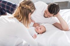 jonge ouders die met weinig babyjongen liggen royalty-vrije stock afbeeldingen