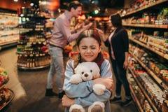 Jonge ouders en dochter in kruidenierswinkelopslag Zij zit in karretje en omhelst stuk speelgoed draagt Het meisje houdt ogen ges royalty-vrije stock foto