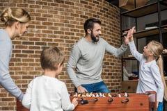 jonge ouders en kleine jonge geitjes die lijstvoetbal samen spelen stock afbeeldingen