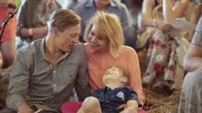 Jonge ouders met hun aanbiddelijke zoon bij de binnengebeurtenis stock videobeelden