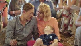 Jonge ouders met hun aanbiddelijke zoon bij de binnengebeurtenis stock video