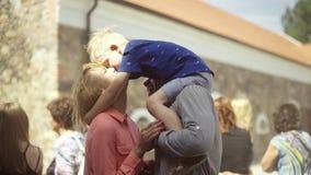 Jonge ouders met hun aanbiddelijke zoon die en pret in binnenplaats kussen hebben stock footage