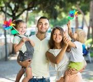 Jonge ouders met kinderen die windmolens spelen Stock Fotografie