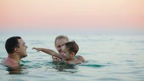 Jonge ouders met zoon het baden in overzees stock footage