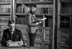 Jonge ouderwetse schrijver met schrijfmachine in bibliotheek met gebaarde vriend royalty-vrije stock foto