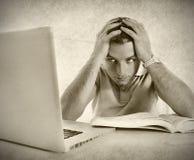 Jonge overweldigde studentenmens in spanning het bestuderen van examen met boek en computer royalty-vrije stock afbeeldingen