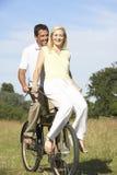 Jonge paar berijdende fiets in platteland royalty-vrije stock afbeelding