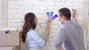 Jonge paar en kleurenmonsters om een muurdecoratie te selecteren stock videobeelden