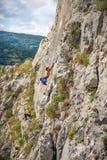 Jonge paar en tiener die op de rots beklimmen stock fotografie