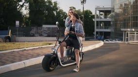 Jonge paar het besteden tijd samen Het aantrekkelijke meisje sluit vriend` s ogen van de rug Hij de zitting van ` s op een fiets stock footage