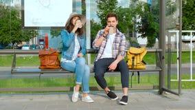 Jonge paar het drinken koffie die in openlucht op een busstationbank zitten stock videobeelden