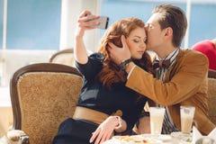 Jonge paar het letten op foto's op een mobiele telefoon Stock Fotografie
