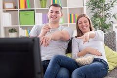 Jonge paar het letten op televisie stock afbeeldingen