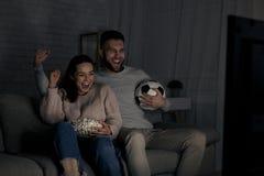 Jonge paar het letten op voetbalwedstrijd op televisie stock fotografie