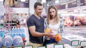 Jonge paar het plukken Pompelmoes in een supermarkt stock videobeelden
