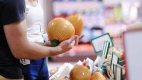 Jonge paar het plukken vruchten in een supermarkt stock video
