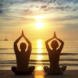 Jonge paar het praktizeren yoga op het strand tijdens zonsondergang stock afbeelding