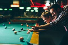 Jonge paar het spelen snooker samen in bar stock fotografie