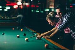 Jonge paar het spelen snooker samen in bar royalty-vrije stock foto