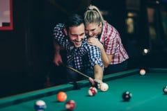 Jonge paar het spelen snooker samen in bar stock foto