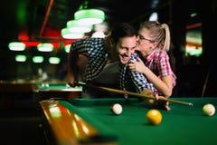 Jonge paar het spelen snooker samen in bar royalty-vrije stock afbeelding