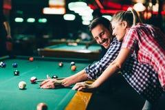 Jonge paar het spelen snooker samen in bar royalty-vrije stock fotografie