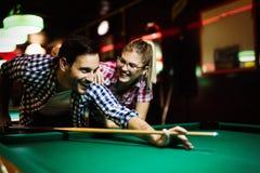 Jonge paar het spelen snooker samen in bar royalty-vrije stock afbeeldingen