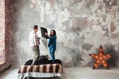 Jonge paar het vechten hoofdkussens in de slaapkamer van de zolderstijl Royalty-vrije Stock Foto's